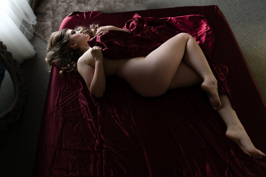 red satin sheets blonde laying down naked